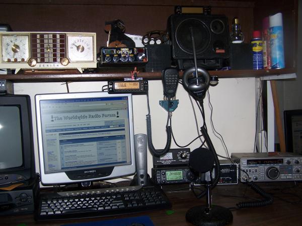 Desk of stuff.  Zentith AM clock radio, Uniden PC66XL, Icom IC706MKIIG, Kenwood TS430S, Yaesu FT 8100, MFJ meters.