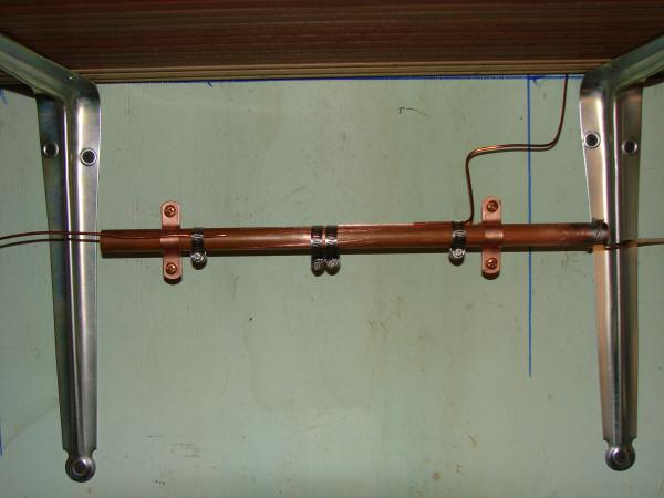"My station ground system with a 1/2"" copper pipe bus bar, and ground leads connected via stainless steel hose clamps...."