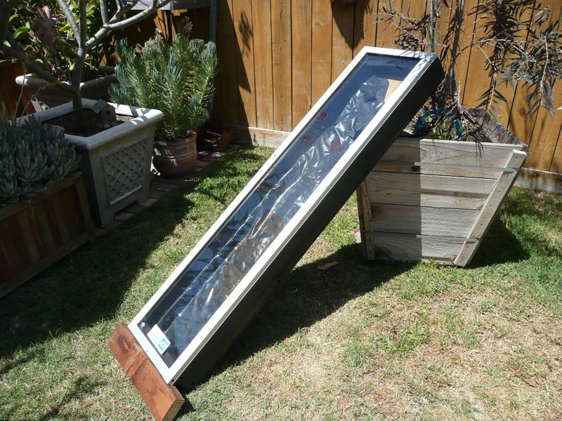 "Making a new solar 'collector' from a discarded 'doggy door' insert (from a sliding glass door cut down to 54""x15""). The box is constructed from 2 x 4s and 3/8"" plywood (painted black)."