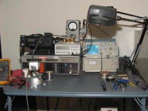 Tech bench: small but effective.  Marconi 10khz - 520Mhz signal generator, Fluke PM6666 1.3GHz Frequency couter, Tektronix  2336 100Mhz O-scope, Bird 43P with ots of slugs, Fluke DMM, and Weller soldering station.  Yaesu 897D for monitoring purposes.  Thi
